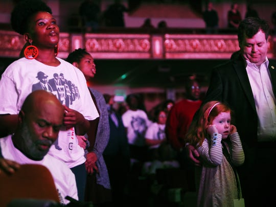 "February 24, 2018 - Philip Davis looks at his 6-year-old daughter, Rachel, as she covers her ears during a performance by the Tennessee Mass Choir during the rendition of ""Lift Every Voice and Sing"" during the I AM A MAN Commemoration at the Orpheum Theater on Saturday morning. The event, hosted by the City of Memphis, recognized sanitation workers involved in the 1968 Sanitation Strike."