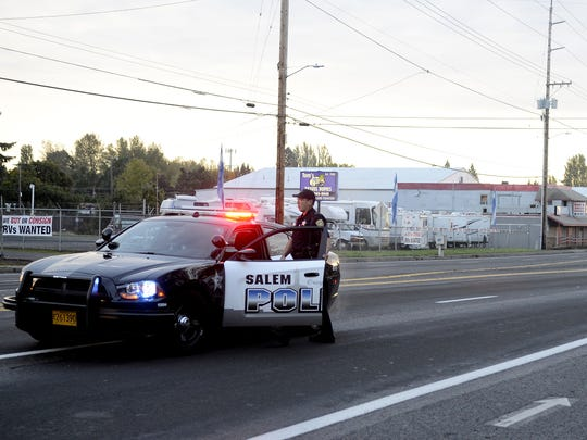 A Salem police officer opens up State Street and 37th Ave. SE following an officer-involved auto accident at State Street and Lancaster Road in Salem on Monday, Oct. 27, 2014.