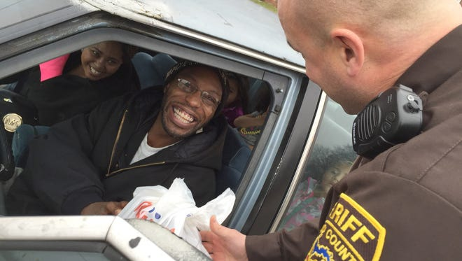 After being pulled over for a minor speeding violation near downtown Pontiac, Mich., resident Darius Crowder, 47, instead gets a Christmas ham Dec. 23, 2014, from Capt. Tim Atkins of the Oakland County Sheriff's Office, one of 300 hams that county deputies handed out.
