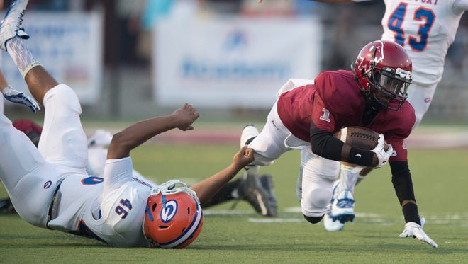 Prattville DeKeith Whatley is tripped up by Gulfport's Gabriel Williams during the game on Friday, Sept. 4, 2015 in Prattville, Ala.