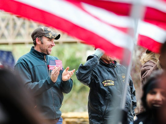 Josh Reidenbaker claps as marchers pass for the Lone Star Warriors Outdoors parade Thursday.