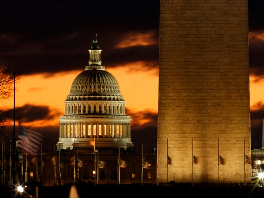 The U.S. Capitol dome is seen past the base of the Washington Monument just before sunrise in Washington. Hundreds of thousands of federal workers have been placed on furlough or are being forced to work without pay because a fight over border wall funding has shut down a quarter of the federal government.