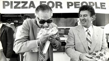 In 1985, Detroit Mayor Coleman Young eats a slice of pizza at a fundraiser for the hungry in Detroit. It was sponsored by Little Caesars Pizza, owned by Mike Ilitch.