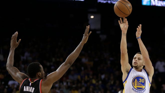 Golden State Warriors' Stephen Curry, right, shoots over Portland Trail Blazers' Al-Farouq Aminu, left, during the second half of an NBA basketball game Sunday, April 3, 2016, in Oakland, Calif.