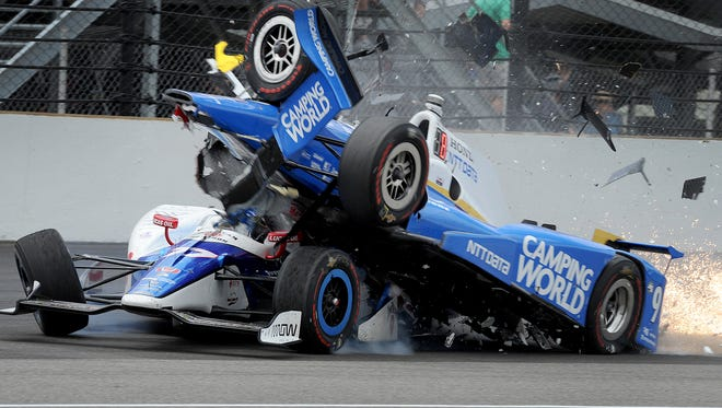 Chip Ganassi Racing IndyCar driver Scott Dixon (9) runs over Schmidt Peterson Motorsports IndyCar driver Jay Howard (77) coming out of tune one during the 101st running of the Indianapolis 500 at Indianapolis Motor Speedway Sunday, May 28, 2017.