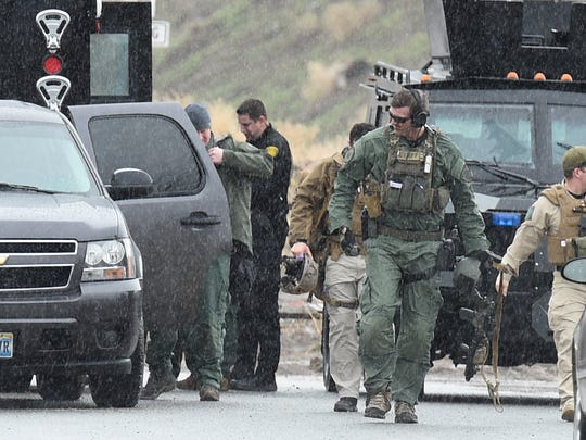 The Sheriff's SWAT team returns from securing the area where two people where found dead inside a vehicle in southeast Reno on Thursday.