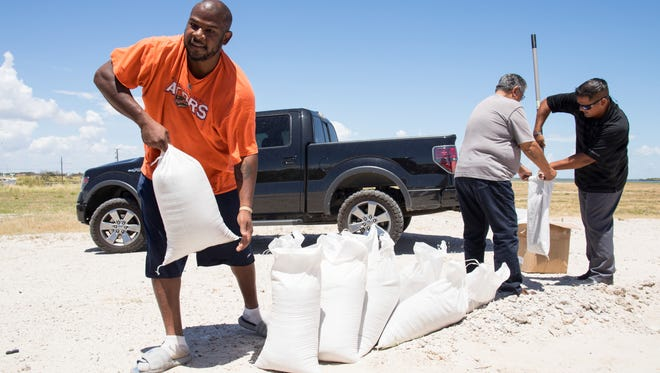People fill sandbags behind the Seaman's Memorial Tower in Aransas Pass, Texas, ahead of a tropical storm on Aug. 23, 2017. Texas Gov. Greg Abbott has ordered the State Operations Center to elevate its readiness level and is making state resources available for preparation and possible rescue and recovery actions amid forecasts a tropical storm will make landfall along the Texas Gulf Coast.