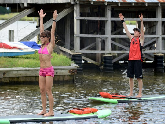 Lisa Rodriguez-Long leads a student through some stretches on paddle boards. SUP yoga tests participants' balance with traditional yoga poses, such as downward dog, the tree pose and the warrior pose.