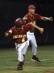 Florida High Coach John Hollenbeck signals Eric Marshall to steal home after a teammate stole second base and collided with a Madison County player. Marshall, who received a kidney transplant from his father in June 2000, slid home and scored.