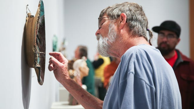 Roger Allen, director of the Old Chicken Farm Art Center, points out details April 18, 2016, at the San Angelo National Ceramic Competition at the San Angelo Museum of Fine Arts, 1 Love St.