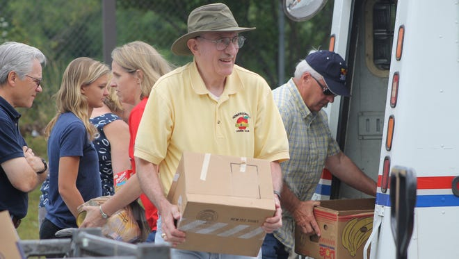 Volunteers help unload and sort donated food collected by letter carriers in Henderson County.
