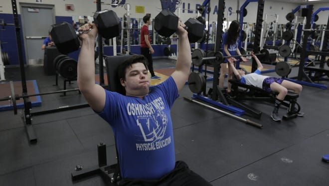 Junior Cole Woldt works out Monday afternoon in the Oshkosh West High School weight room. The school is raising money to beef up the facility to modernize it and make it more competitive within the conference as part of a $80,000 renovation.