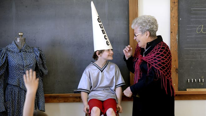 In this Friday May 23, 2014 photo, Lockwood Elementary School second grader Noah Shelden, 8, is the first to try on the dunce cap as Carol Williams of the Eaton Rapids Area Historical Society teaches about one room schoolhouses to the schoolchildren touring the historic Miller Farm in Eaton Rapids, Mich.