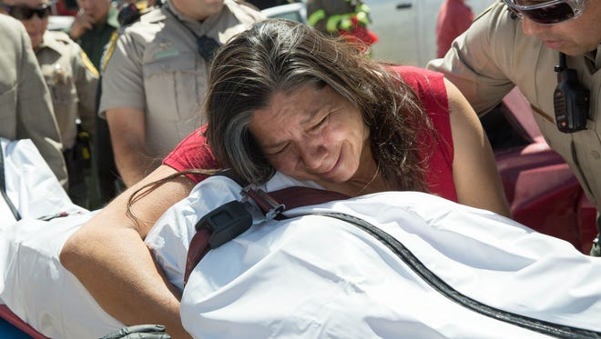 "Carmen Martinez, portraying the mother of Amy Ulmer, clutches Ulmer's body as she is taken away by law enforcement and funeral home workers in a mock DWI and distracted driving accident, part of the Shattered Lives program. Ulmer and other Santa Teresa High School Students participated in the mock accident to help teach fellow students  about the dangers of driving while intoxicated and driving while distracted. Thursday April 27, 2017, The students in the mock accident would remain, ""dead"" for a day ."