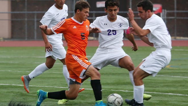 Mamaroneck's Cole DiCicco (5) tries to get around New Rochelle's Javier Amezcua (25) and Andrew Sirota (6) during boys soccer action at New Rochelle High School Oct. 5, 2017. DiCicco scored the only goal of the game in Mamaroneck's 1-0 victory,