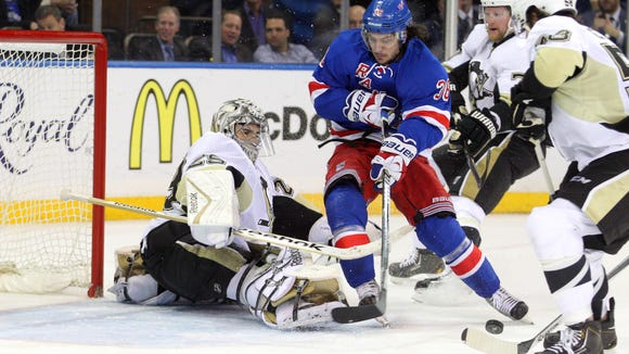 Pittsburgh Penguins goalie Marc-Andre Fleury stops Rangers right wing Mats Zuccarello during the third period of Game 3 on Monday night.