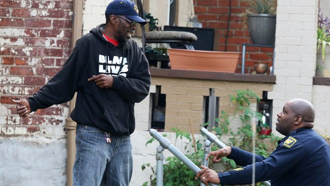Cincinnati Police officer  Deon Mack, right, talks with a man who lives on Rice Street in Mount Auburn, Tuesday November 1, 2016, near the scene of where Sam DuBose was killed in July 2015. The jurors in the murder trial of former University of Cincinnati police officer Ray Tensing where making a trip to view the scene that day.