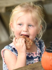 Mae Daily, 2, tucks into a spice doughnut at Erwin's