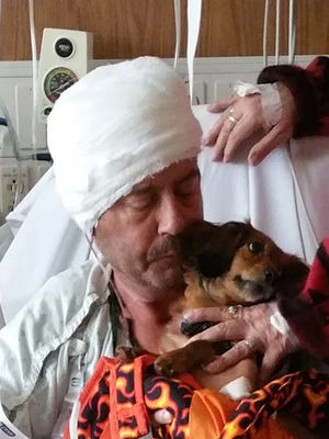 Steve Miller pictured in the hospital with his dog after being assaulted by his neighbor for blowing leaves off his property when the leaves went on his property.