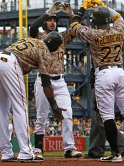 Pittsburgh Pirates' Matt Joyce (17) celebrates with teammates Andrew McCutchen (22) and Gregory Polanco (25) after hitting a three run home run off Milwaukee Brewers starting pitcher Matt Garza in the first inning of a baseball game in Pittsburgh, Thursday, July 21, 2016. The Pirates won 5-3.