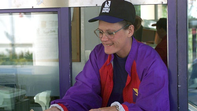 This is a 1999 photo that shows Denise Steward handing food to a drive-thru customer at a Hot 'n Now in Charlotte.