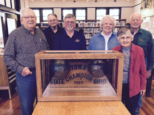 Cliff Woody (from left), Gordon Wait, David White, Martha Randel, Florence Emma Peery and Cliff Beesley surround the trophy for the 1915 Indiana state basketball champions of Thorntown High School at the town's Public Library, 124 N. Market St.