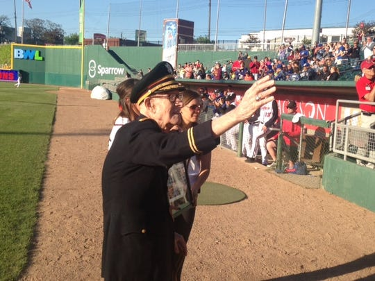 Gilbert Holmes, 97, of Holt, waives to the crowd during a special tribute to him at Cooley Law School Stadium on Friday night. Holmes served nearly 40 years in the Army and Michigan National Guard.