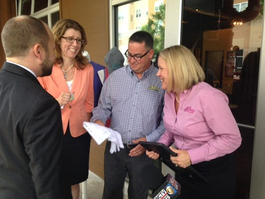 """Danny and Tracey Shrine, owners of Full Press Apparel on Gaines Street, share a laugh with County Commissioner Kristen Dozier during Thursday's press conference. The company was recognized by the Greater Tallahassee Chamber of Commerce in the """"Made in Tallahassee"""" campaign highlighting local businesses with national and global clients."""