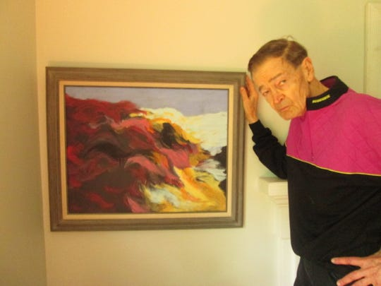 Chicago artist Paul Brewer, a native of Alexandria, poses with one of his landscape paintings.
