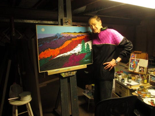 Alexandria native Paul Brewer poses by one of his paintings in the basement studio of his home in Lake Forest, Illinois.