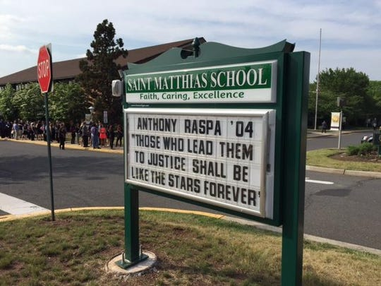 A sign outside St. Matthias Roman Catholic Church in Franklin pays tribute to Trooper Anthony Raspa.