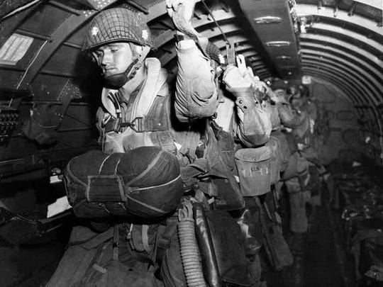 U.S. paratroopers fix their static lines before an early dawn jump on D-Day June 6, 1944, in Normandy, France.