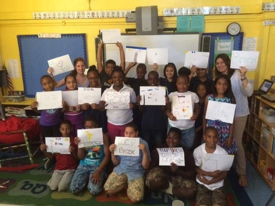 The fourth-grade class at PS 62 in the Bronx holds signs expressing sadness at the death of the peregrine falcon in Rochester that they named. Webcams trained on the falcons' nest were used daily as a learning tool by co-teachers Suzanna Lull, left rear, and Valerie DellaCerra, right rear.
