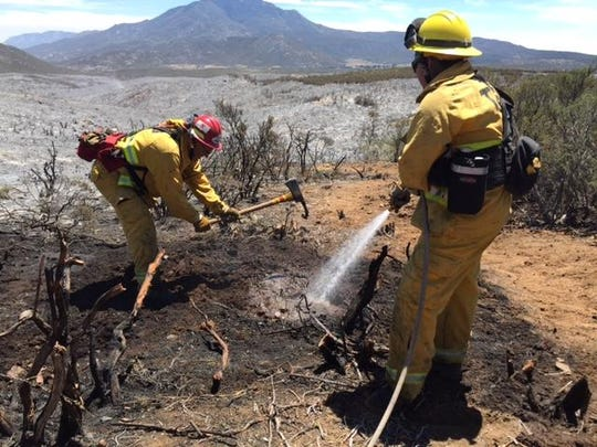 From left, Capt. Charles Steinway and firefighter Sarah Nino of the Tulare County Fire Department mop up Anza Fire hotspots on Tuesday. A motor home that caught fire around noon Monday on Highway 74, at the Highway 371 junction in Anza, ignited some dry brush. The fire quickly grew to 487 acres and caused some evacuations Monday.