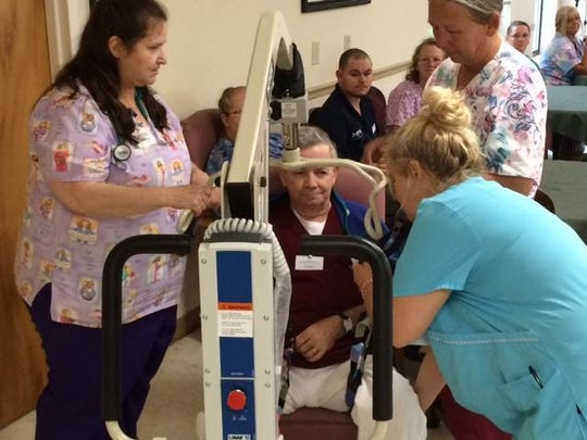 Certified nursing aides, including Stephen Deaver, center, play-act the incorrect way to lift a patient during an in-service workshop at Emerald Ridge Rehabilitation and Care Center. The idea was to show how improper behavior such as brusquely handling patients or talking down to them makes patients' lives more difficult.