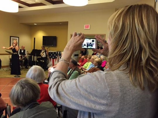 Mary Hilsabeck, Engage Life Director at Atria Hacienda, shoots video of Terri Owens singing 'God Bless America' at the conclusion of the Spirit of '45 ceremony on Friday, Aug. 14, 2015.
