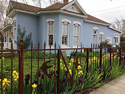 Paula Voris' home and garden in the Alameda Depot District features a cattails and swallow fence that was inspired by an old photo from the days of Grace and Elias Day, who designed and built the home. Nick Fresquez, owner of Essential Elements, created the fence.