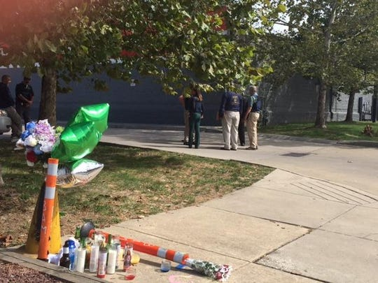A memorial for Jeremy McDole stands in the foreground as state investigators inspect the area where he was shot to death by city police on Wednesday.