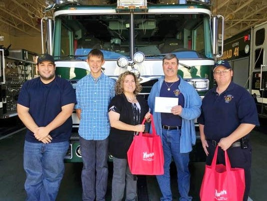 """Julie Martin, center, presents a donation along with """"thank you"""" bags Monday for each emergency responder to the Franklin Fire Company who helped put out a tractor-trailer that caught fire in September at the Martin's facility in the 1000 block of Potato Roll Lane."""