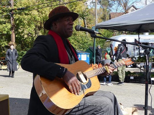 Blues musician Paul Miles entertains customers at the Birmingham Farmer's Market. The market brings in different entertainers throughout the season.
