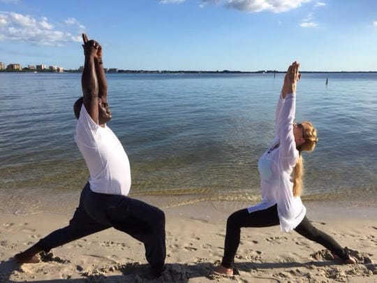 Yoga instructor Sheryl Purnell, right, leads a student in performing the warrior one, a standing yoga pose.