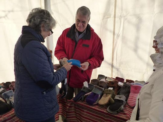 Terry Bennett of the Green Mittenry in Canton shows off a handmade mitten created from a recycled sweater.