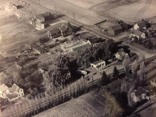 An aerial shot from the late 1960s or early 1970s shows the original Rockcastle store and greenhouses.