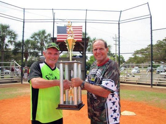 League Commissioner Bill Shurina presents SpeakEasy manager Ray Kane of Speakeasy with the Island Division tournament Trophy.