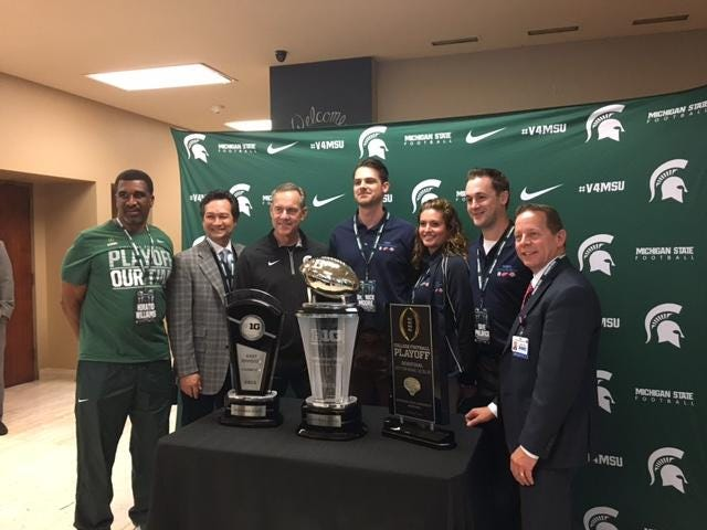 Michigan State coach Mark Dantonio, third from left, and others pose Wednesday in Detroit with trophies for winning the Big Ten East, the Big Ten championship game and making it to the College Football Playoff.