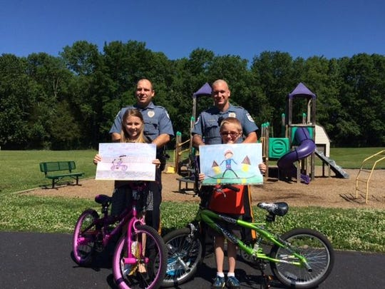 "Andover Twp. Police Officers Edward Diklich (left) and Puccio (right) present the first place winners of their ""Wheels Under Your Feet, Helmets On Your Head"" poster contest with their bicycles."