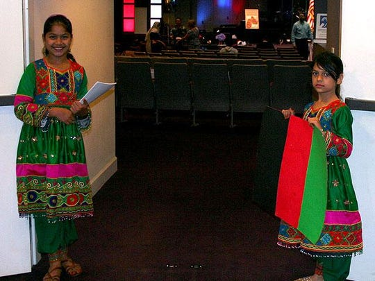 Two students from Sable Palm Elementary, originally from Afghanistan, handing out agendas for Thursday's event for World Refugee Day at Freedom Church, Thomasville Road.