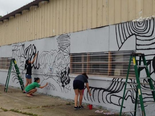 Students create art on an old warehouse wall.