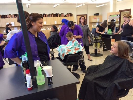 Natalia Contreras/Caller-Times Kimberly Carrera (left) chats with Jessica Milligan about heading back to school. Jessica got a free back-to-school haircut Monday by the Del Mar College dual credit cosmetology students.