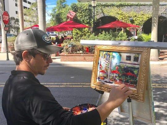 Street artist Lazaro Morera paints the scene at Clasico's